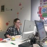 Eine junge Frau in einer karierten Bluse sitzt an einem Schreibtisch und arbeitet am Computer.