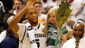 An image of Adreian Payne carrying Lacey Holworth after the Iowa-Michigan game