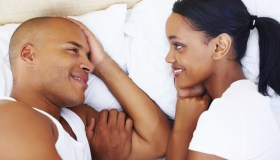 Smiling couple in bed looking at each other