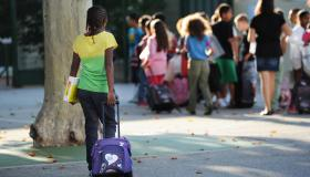 A pupil arrives in the courtyard of the Abbe de l'Epee elementary school on September 3, 2013 in Marseille, southern France, prior to enter her classroom on the first day of school. More than 12 million pupils went back to school today in France