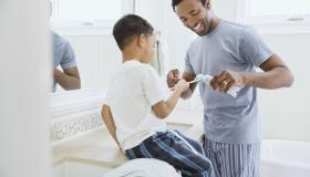 Father squeezing toothpaste on son's toothbrush in domestic bathroom