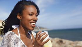 Young woman drinking fruit juice at beach, Malibu, California, USA