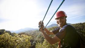 Guy smiling with hands on zip line over tree tops