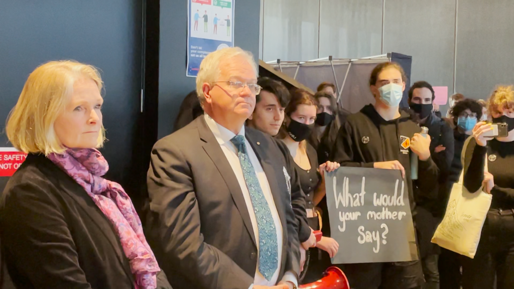 Brian Schmidt AC and Grady Venville, surrounded by student protestors who are expressing their discontent with the ANU's lack of action on a Human Rights Commission report into sexual harassment and assault on campus.