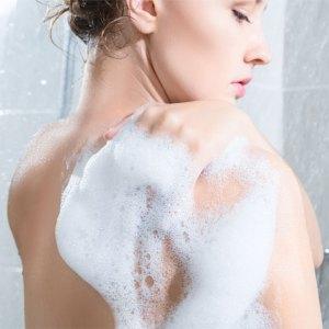 femme sous la douche avec de la mousse de la poudre de douche iovana
