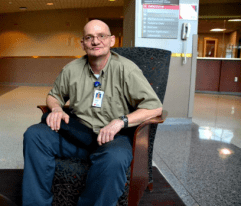 Michael Lentz smiling sitting in a chair in the hospital lobby at Nebraska Medicine.