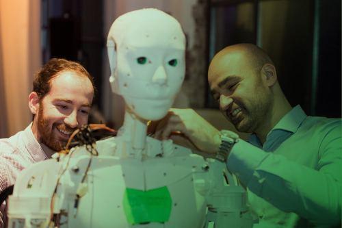 Zum Artikel Internet of Everything: Zwei Personen arbeiten an der Technik eines humanoiden Roboters