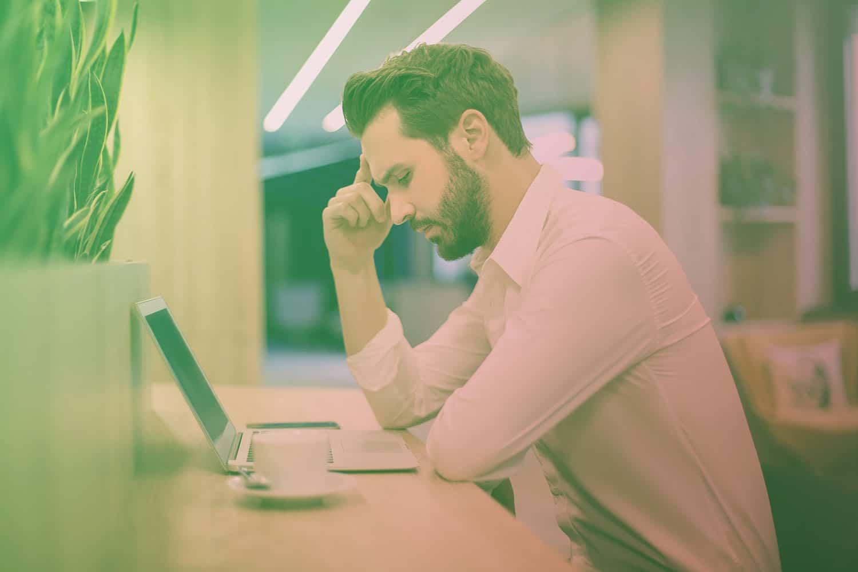 Zum Artikel IoT Pain Points: Mann sitzt am Schreibtisch und hält sich an der Schläfe, Laptop und Kaffee auf dem Tisch