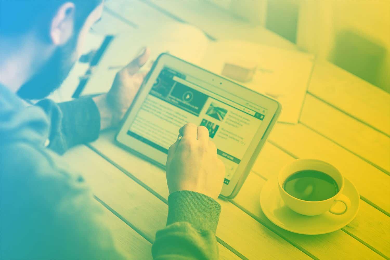 Zum Beitrag Best-of IOX IoT Blog: Mann am Tablet, Kaffee auf dem Tisch