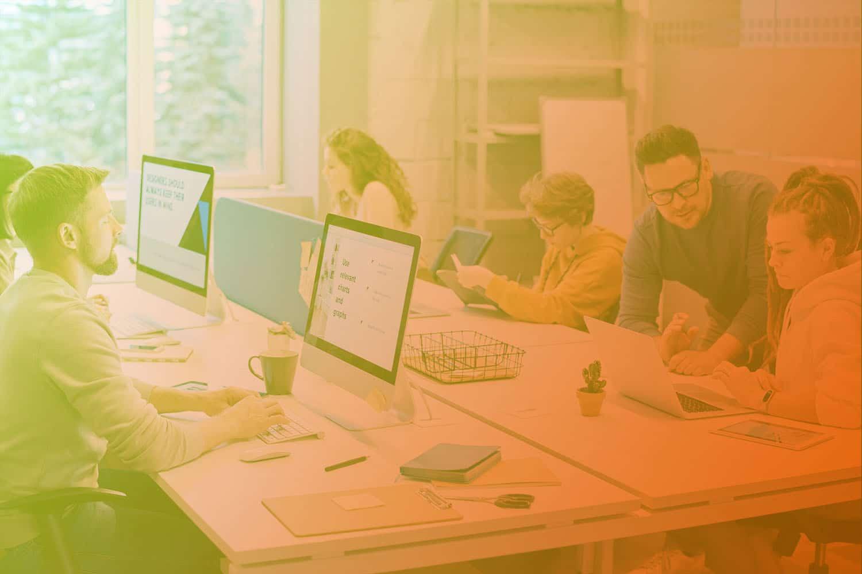 Zum Thema IoT-Projekte umsetzen: Personen am Schreibtisch, Laptop, Schreibutensilien