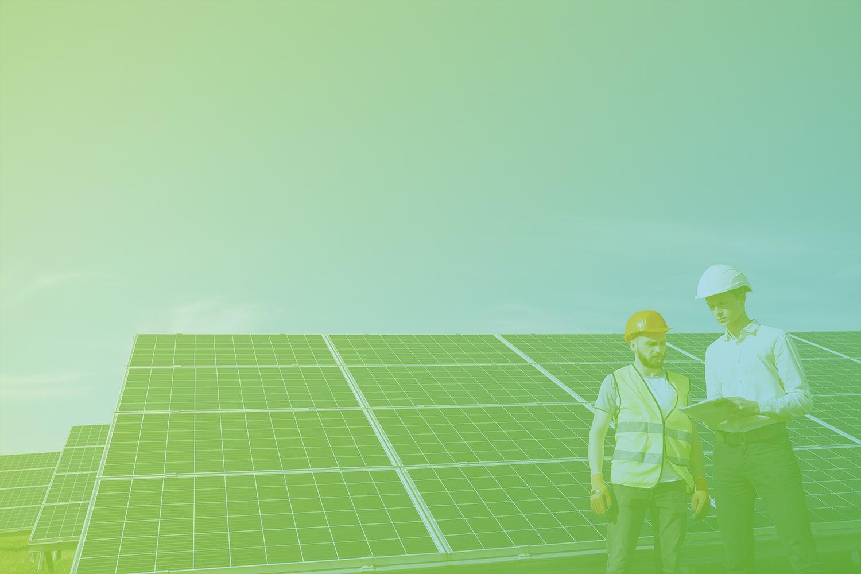 Zum Artikel IoT Lösungen für die Energiewirtschaft: Zwei Männer vor Solaranlagen auf einem Feld