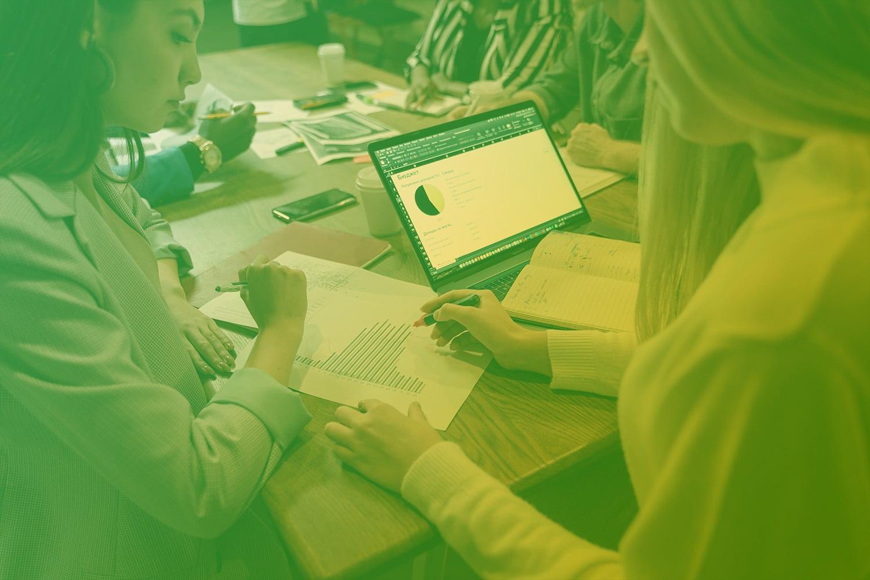 """Zum Artikel """"In 10 Schritten zum erfolgreichen IoT-Geschäftsmodell"""": Personen am Tisch mit Laptop, Zetteln und Disgrammen"""