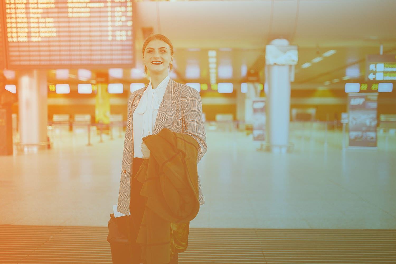 Zum Beitrag Digitalisierung der Luftfahrt: Frau mit Jacke über dem Arm und Koffer in Flughafen-Halle