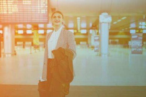 Zum Beitrag Digitalisierung der Luftfahrt: Frau mit Jacke und Koffer in Flughafenhalle