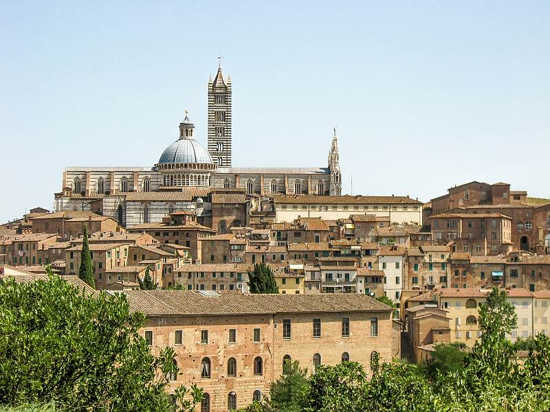 medieval yellowish houses on a hill with a church with a dome and a bell tower on a hill, Siena in Tuscany Italy