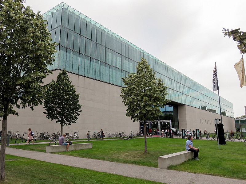 a long building with a second floor out of glass and a green lawn in front, Museum of the Egyptian Art in Munich Germany