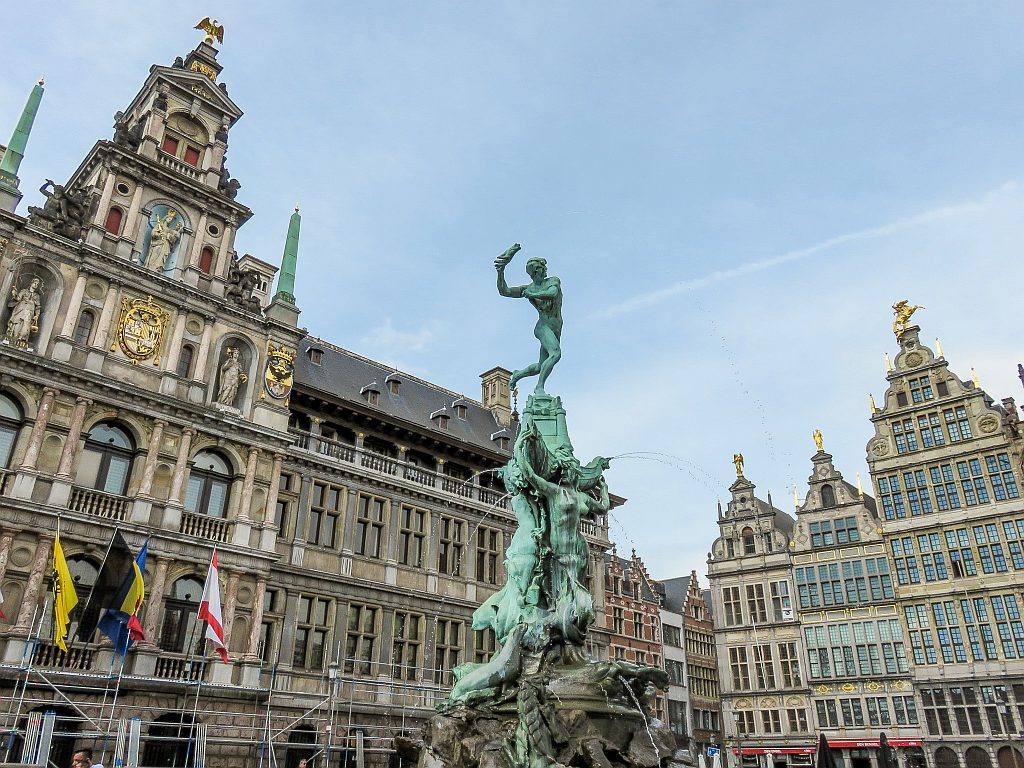 a fountain with a male figure throwing a hand and buildings with flags on them at the background, Antwerp Belgium