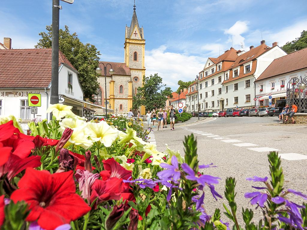 colourful flowers on the foreground, a small square and a church at the background, Hluboka nad Vltavou in South Bohemia, Czech Republic