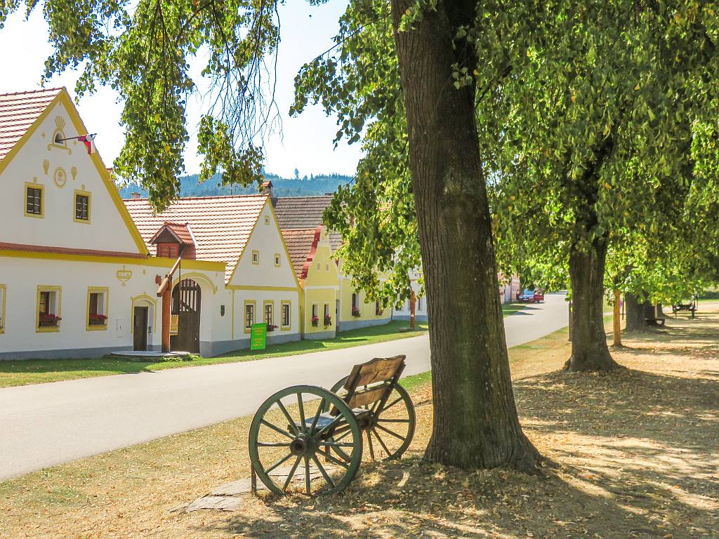 a bench, trees, a street and houses in various colours with ornamented facades, Holasovice in South Bohemia, Czech Republic