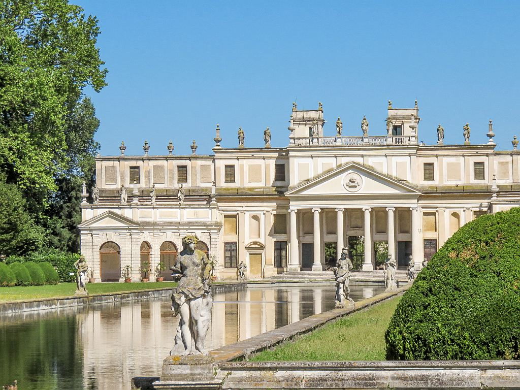 a white large building with columns and water canal in front of it lined up with statues, Villa Pisani along the Brenta Canal