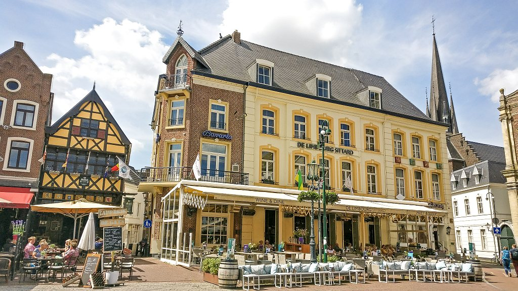 yellow building with cafes and one half-timberd house, the square in Sittard Limburg