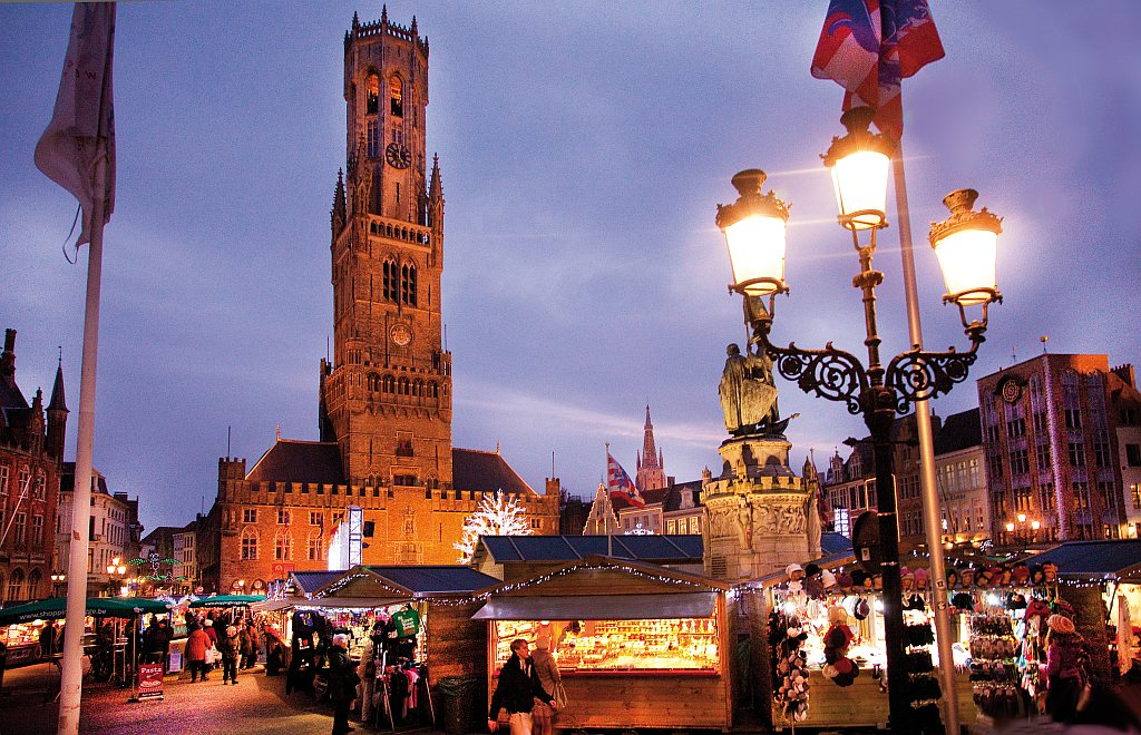 a high belfry with a clock and Christmas markets stalls on a square in the evening; the Christmas market in Bruges