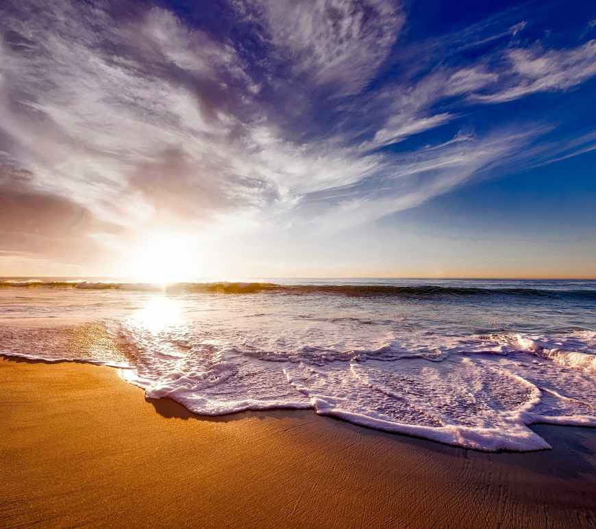 seashore under white and blue sky during sunset