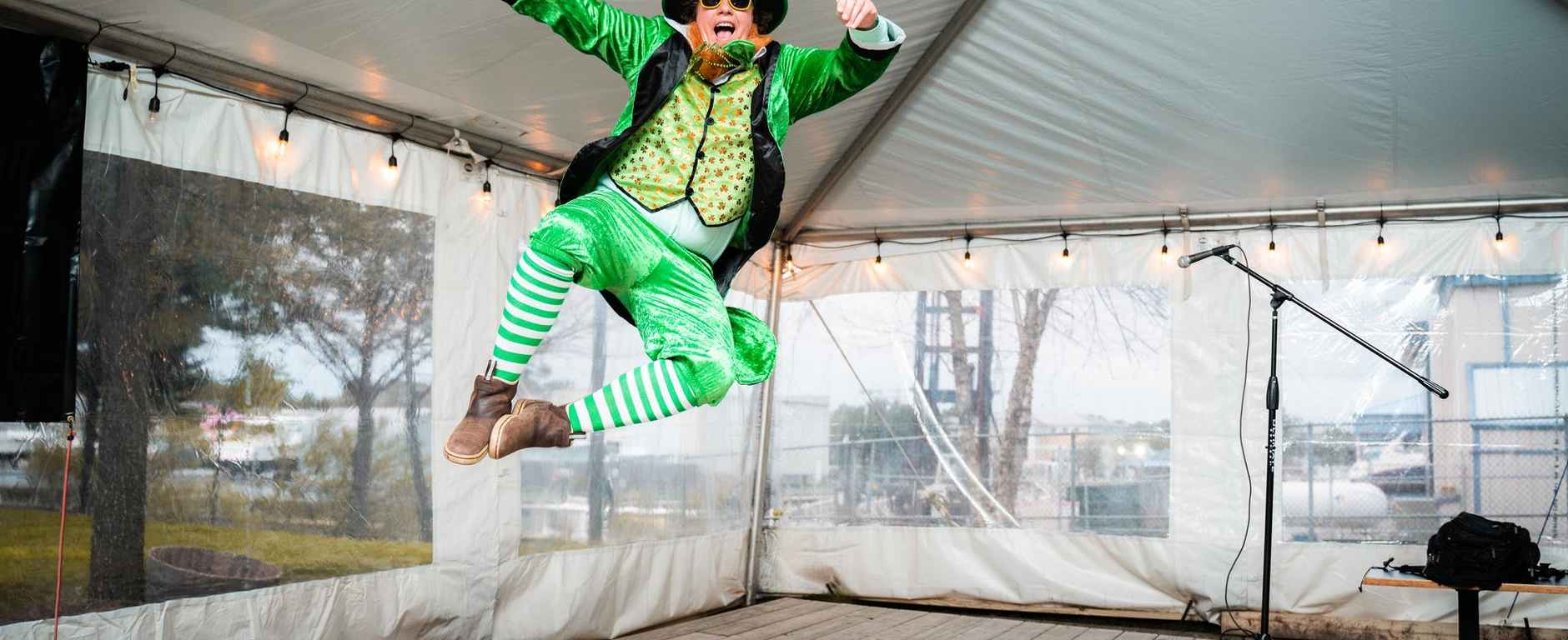 cheerful anonymous circus artist in colorful costume jumping in tent