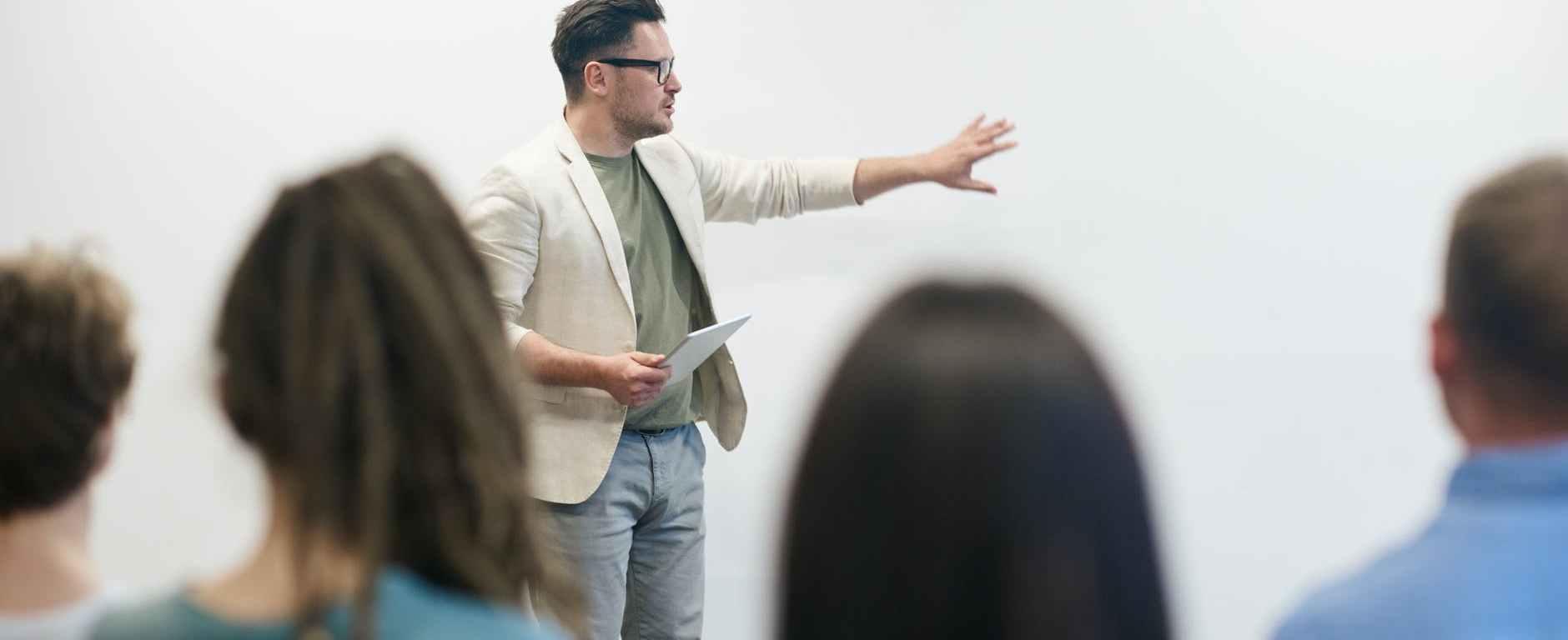 man in beige blazer holding tablet computer