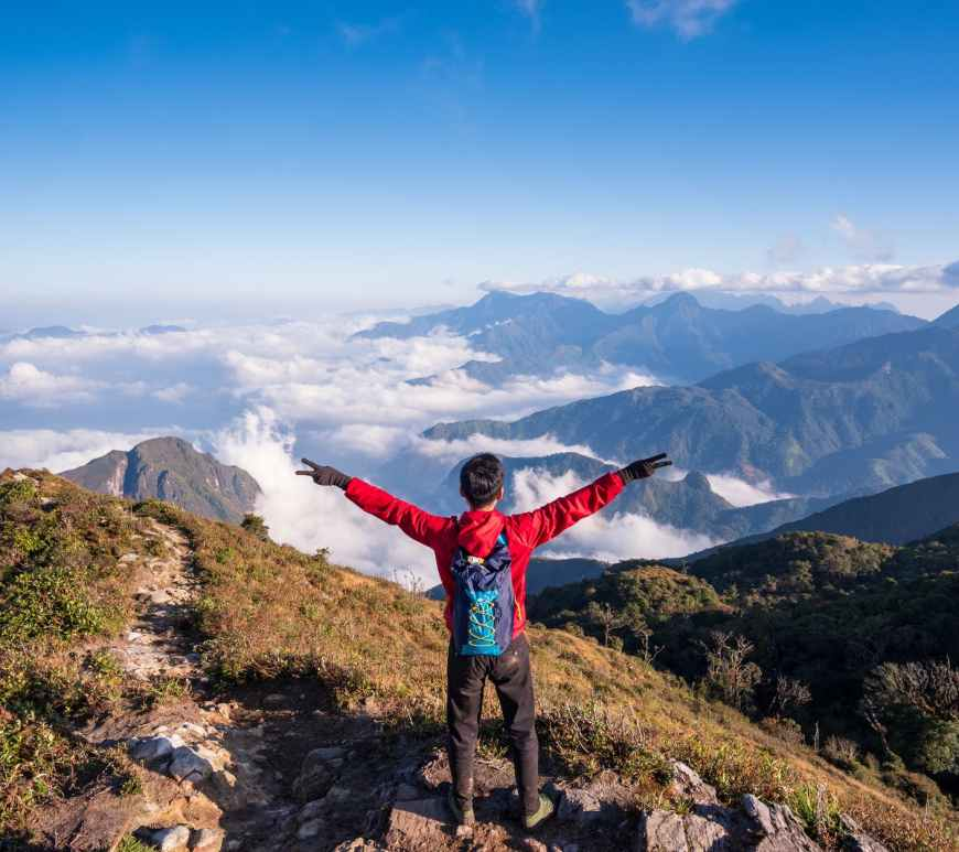 photo of man standing on mountain while doing peace sign