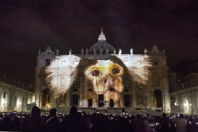 epa05060413 A view of Saint Peter's Basilica facade illuminated as part of a contemporary public art projection entitled 'Fiat Lux: Illuminating our Common Home' to Pope Francis on the opening day of the Extraordinary Jubilee of Mercy, in Rome, Italy, 08 December 2015. EPA/GIUSEPPE LAMI