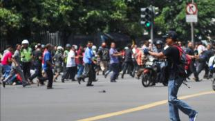 In this photo released by China's Xinhua News Agency, an unidentified man with a gun walks in the street as people run in the background on Thamrin street near Sarinah shopping mall in Jakarta, Indonesia, Thursday, Jan. 14, 2016. Suicide bombers exploded themselves in downtown Jakarta on Thursday while gunmen attacked a police post nearby, a witness told The Associated Press. Local television reported more explosions in other parts of the city. (Veri Sanovri/Xinhua via AP) NO SALES