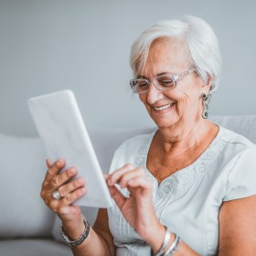 Happy senior woman with tablet PC