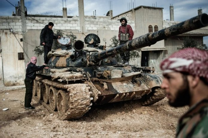 Militants stand around a military tank.