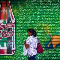 Woman walking in front of Jamaica Plain graffiti