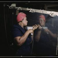 black worker holds hand drill