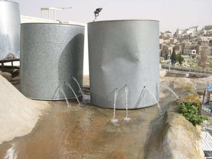 Palestinian water tanks vandalized by Israeli settlers in Hebron. (Photo: ISM Palestine / Flickr)