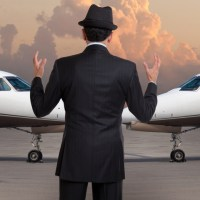 rich person looking at his two private jets