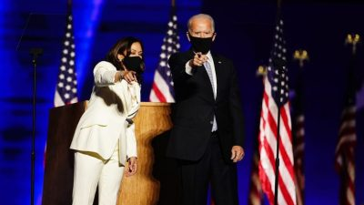Joe Biden and Kamala Harris wearing masks, standing at a lectern pointing towards the audience.