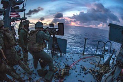 U.S. military firing .50-caliber machine gun in the philipine sea to depict U.S. militarism