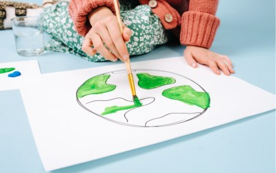biden foreign policy - portrait of teenage girl painting planet earth on paper. Cropped. She uses green color on a brush.