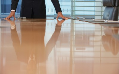 ceo pay - executive standing at a table in a corporate office