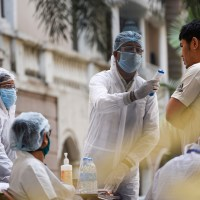 Medics arrive to take blood samples of residents of Spanish Garden residential complex after a COVID-19 positive case was detected in an apartment, in Guwahati.