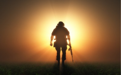 full clad u.s. military soldier walking away into the sunset