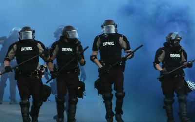 militarized police in swat gear marching toward crowd of protesters with blue smoke in the background