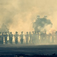 Military police riot response to a protest with tear gas, smoke, fire, explosions