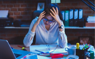 stressed worker pictured at desk during covid pandemic