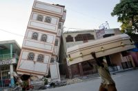 A man carries a coffin past a toppled building in downtown Port-au-Prince. / Credit:UN Photo/Marco Dormino