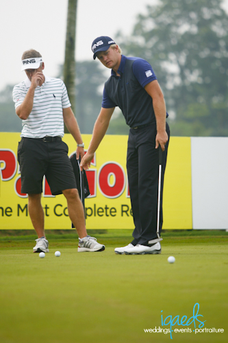 Tom Lewis and his caddy practicing on the practice green
