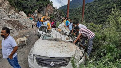 Mandi: People look at damaged vehicles which were hit by falling rocks due to a landslide, on the Chandigarh-Manali highway near Mandi, Saturday, July 31, 2021. (PTI Photo) (PTI07_31_2021_000187B)
